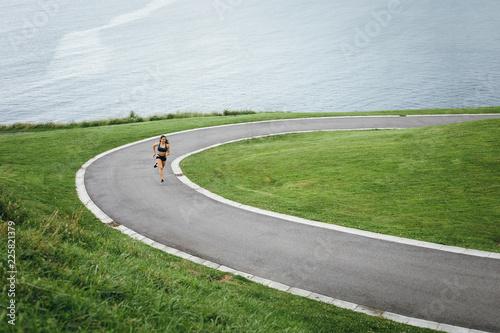 Fototapeta Female athlete running at the park