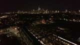night flying over elevated subway in Brooklyn as it approaches Manhattan skyline - 225826187
