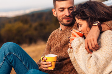Beautiful young couple enjoying picnic time on the sunset. They drinking tea and sitting in a meadow.