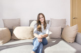 1 white girl with long hair in jeans sitting on the couch, girl smiling - 225841500
