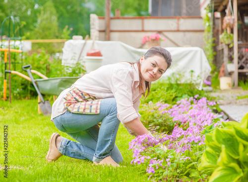 Leinwandbild Motiv Happy woman working in the backyard, caring for flowers