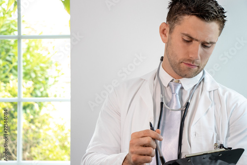Good looking male doctor, gp, with stethoscope and clipboard © Tony Marturano
