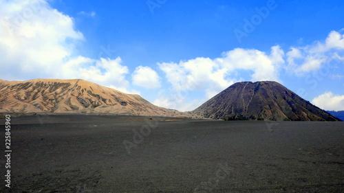 Vulkane Bromo und Batok erheben sich aus dem schwarzen Sandmeer vor blauem Himmel in Ost-Java