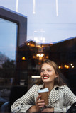 Young beautiful smiling woman in striped trench coat holding cup to go in hand happily looking aside while spending time in cafe - 225854151