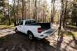 Quadro white pickup car with opened truck in forest