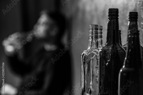 Close-up on alcohol bottles and blurred drunk person in the background