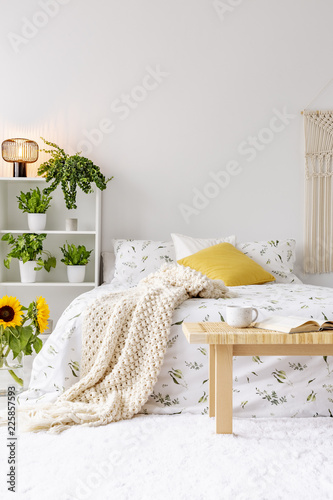 Leinwandbild Motiv Sunny spring bedroom interior with green plants beside a bed dressed in eco cotton linen. Yellow accents. Empty white background wall. Real photo.