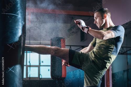 Młodego człowieka trening kopnięcie na uderza pięścią torbie w gym.