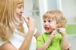 Leinwandbild Motiv Beautiful mother and kid son brushing teeth in bathroom