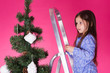 Leinwandbild Motiv Christmas and holiday concept - A little girl is decorating Christmas tree on pink background
