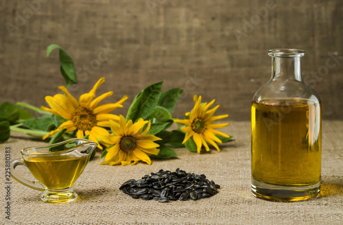 Sunflower oil in a glass gravy boat and a bottle, and a handful of sunflower seeds on the background of burlap and sunflowers.