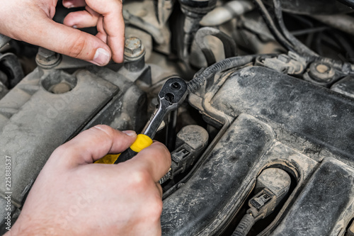 Hands of car mechanic with wrench. Car engine repair.