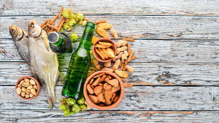Background beer and snacks. Hops, beer, chips, nuts. On a white wooden background. Free space for text. Top view.