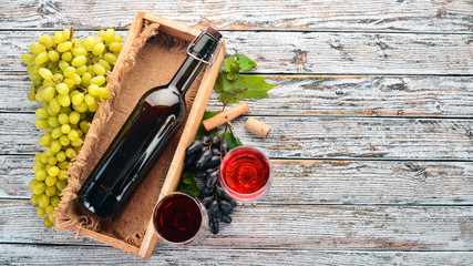 Red wine in a bottle with a glass and grapes. On a white wooden background. Free space for text. Top view.