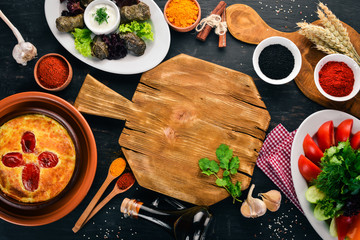 Assortment of dishes of Georgian and European cuisine. On the old wooden background. Free space for text. Top view.