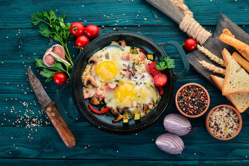 Traditional Israeli Cuisine dishes Shakshuka. Eggs with bacon and mushrooms. On a wooden background. Free space for text. Top view.