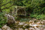 Close up view of small old stone bridge over small river. Bohinj, Slovenia.