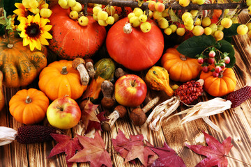 Autumn nature concept. Fall fruit and vegetables on wood. Thanksgiving dinner. Pears and pumpkin with sunflowers and apples.