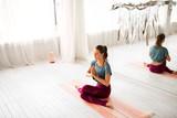 mindfulness, spirituality and healthy lifestyle concept - woman meditating at yoga studio - 225925577