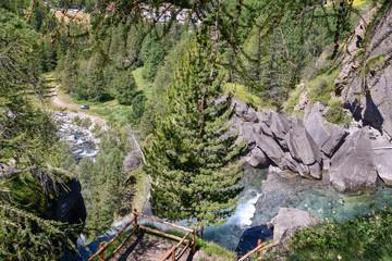 Veduta dall'alto di una cascata tra rocce in montagna d'estate, con foreste e sentieri, Valle d'Aosta, Lillaz, Alpi, Italia © Simona