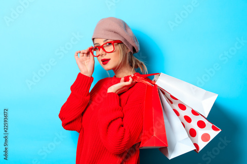 Leinwandbild Motiv Portrait of a young girl in red sweater with shopping bags on blue background