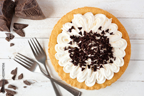 Delicious chocolate cream pie. Top view table scene on a white wood background.
