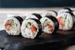 Sushi rolls set on black wooden tray, close up. Asian restaurant menu, food  photo art. Traditional Japanese cuisine