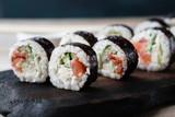 Sushi rolls set on black wooden tray, close up. Asian restaurant menu, food  photo art. Traditional Japanese cuisine © Vadym
