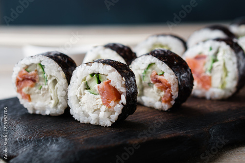 Sushi rolls set on black wooden tray, close up. Asian restaurant menu, food  photo art. Traditional Japanese cuisine