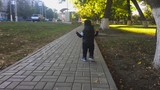 The one year old cute boy is making his first steps in the park. Child make his first steps outdoor. Slow motion video. - 225956184