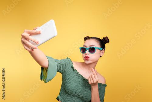 Beztroski i szczęśliwy, modny nastrój. Atrakcyjna azjatykcia kobieta bierze selfies z uśmiechem.