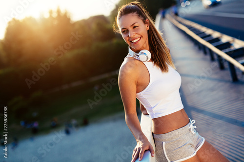 Portrait of woman taking break from jogging - 225986738