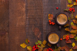 Two brown clay cups of black coffee and branches of autumn leaves (Spiraea Vanhouttei) with small red rowan's fruits on the old wooden table. Top view. - 225997966