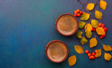 Two cups of black coffee and branches of autumn leaves (Spiraea Vanhouttei) with small red rowan's fruits on a dark blue-green painted wooden table. - 225997996