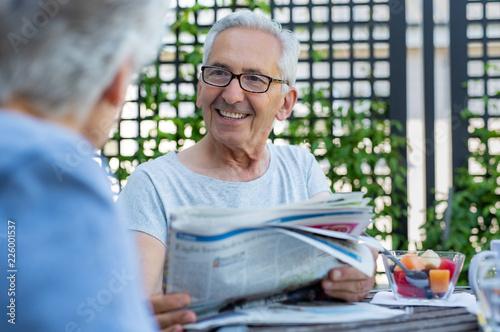 Leinwanddruck Bild Senior man holding newspaper