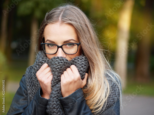 Foto Murales portrait of a beautiful stylish young blonde girl with make-up in black glasses leather jacket and knitted scarf freezes up smiles in the autumn cold park