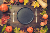 Autumn and Thanksgiving day table setting with fallen leaves, pumpkins, spices, empty black platter and vintage cutlery on brown wooden table. Top view, toned image.