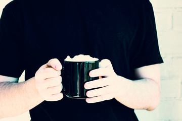 Black mug with coffee drink with cream white topping in the hands of young man in black/ddark blue t-shirt, copy space. Wide panoramic image, Texture white background.