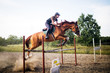 Leinwandbild Motiv Young female jockey on horse leaping over hurdle