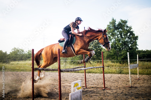 Leinwanddruck Bild Young female jockey on horse leaping over hurdle
