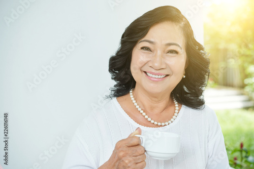 Foto Murales Waist-up portrait of beautiful senior Asian woman with pearl necklace holding cup of tea and smiling at camera cheerfully