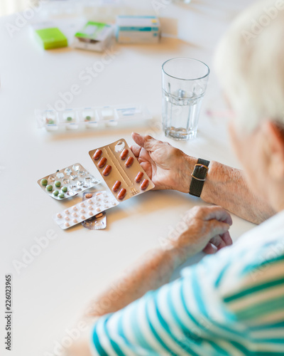 Foto Murales Senior woman holding medicine and pills in her hand