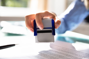 Businesswoman Stamping On Approved Contract Form