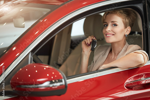 Leinwandbild Motiv Happy driver blonde woman smiling and showing new car key while sitting in a car that she is buying in the auto show. Business, sale for consumerism and people concept.