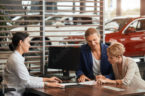 Leinwandbild Motiv Sales agent at the table desk telling about car features to cheerful couple of customers at car dealership office