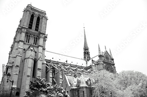 fototapeta na ścianę Notre Dame cathedral (Paris, France) covered with snow in rare snowy winter day. View from the bridge. Black and white photo.