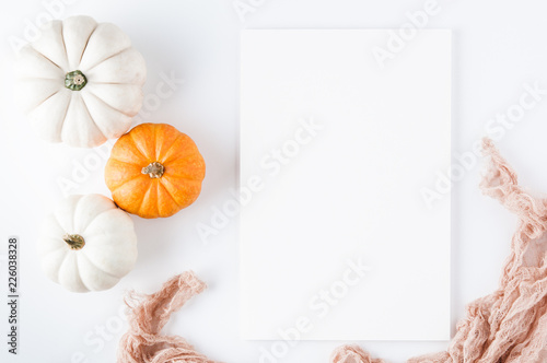 pumpkins beside a blank sheet of paper for a thanksgiving saying
