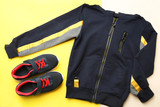 Black sports jacket and sneakers on yellow  beige background. Concept sport.