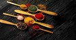 From above view of colorful spices of different sort placed in spoons on wooden background