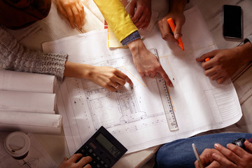 Architect team discussing on blueprints.